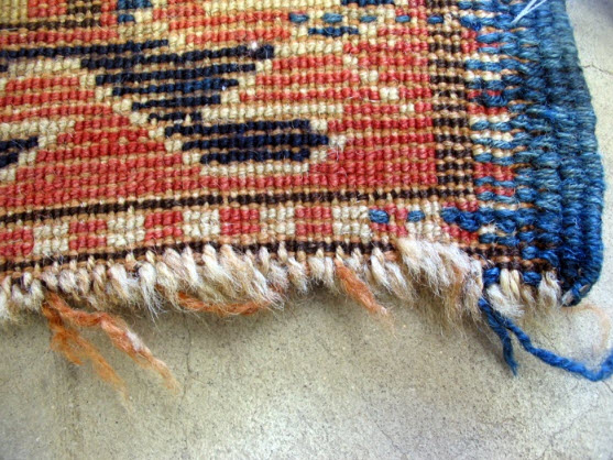 This fringe was cut shorter by the client, but the knots of the rug are now sliding away.