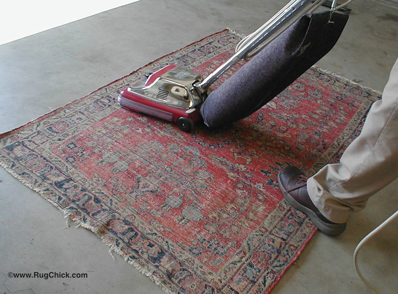 Sarouk rug being dusted