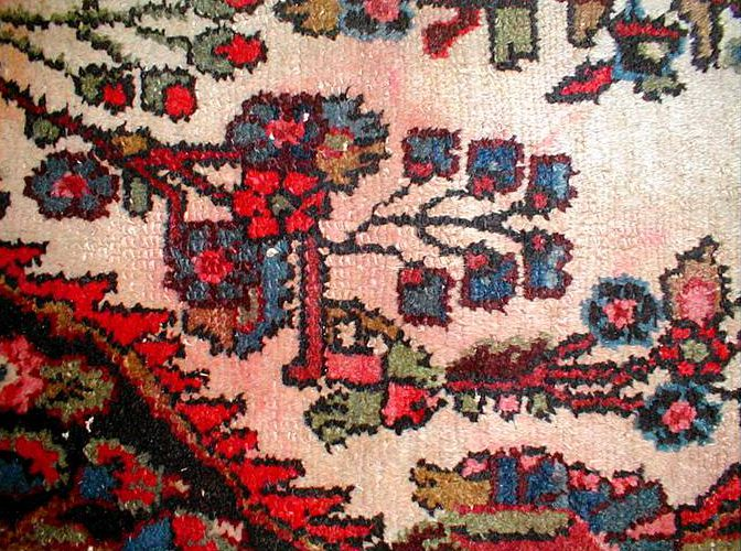 Red dye has bled on the top side of this rug only from an old spill.