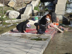 Rugs being washed near a river