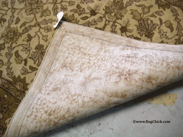Water marks, dye marks, browning marks on the back of a clean tufted rug.