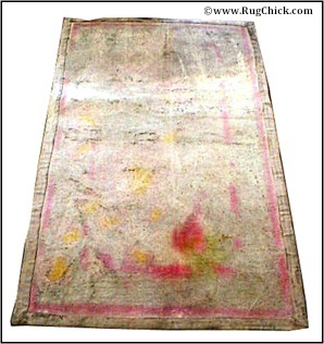 Back of tufted rug – stencil ink bled into backing material.
