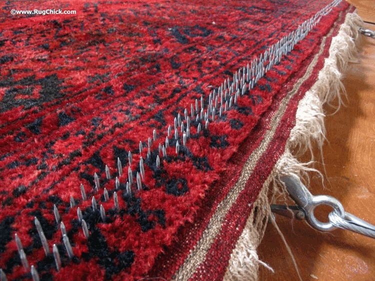 Stretching an Afghan rug to help it lay flatter.