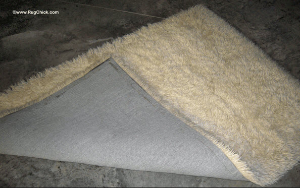 Wool shag rug is yellowing from latex backing and age.