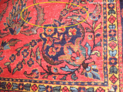 White knots and a little bit of field wear on this Sarouk rug may be left alone because it is expected in a rug of this age, and is not very noticeable at all.