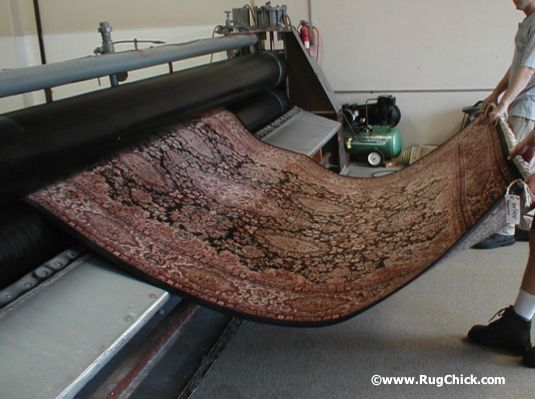 Rug through roller wringer. Safely and quickly removes the excess water and flattens out the rug for quick drying.